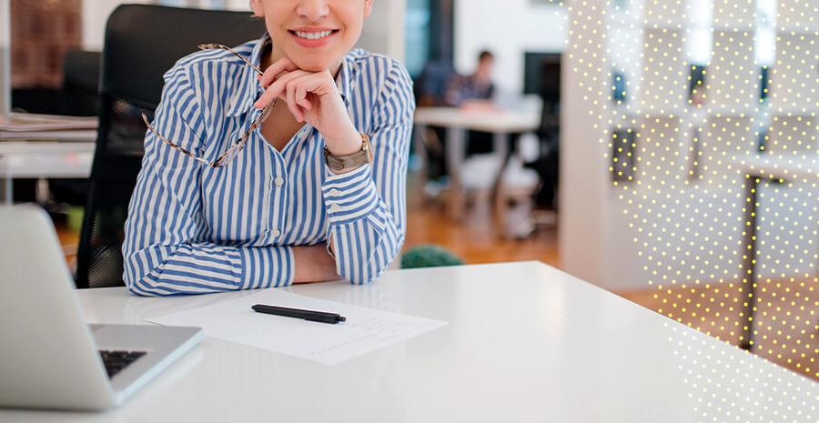imagem de uma pessoa em uma mesa de trabalho sorrindo para a foto