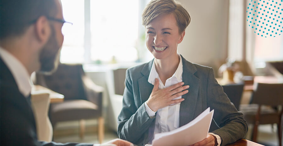 imagem de duas pessoas, um homem e uma mulher, o homem falando olhando para a mulher e a mesma sorrindo com papéis de descrição de cargos na mão