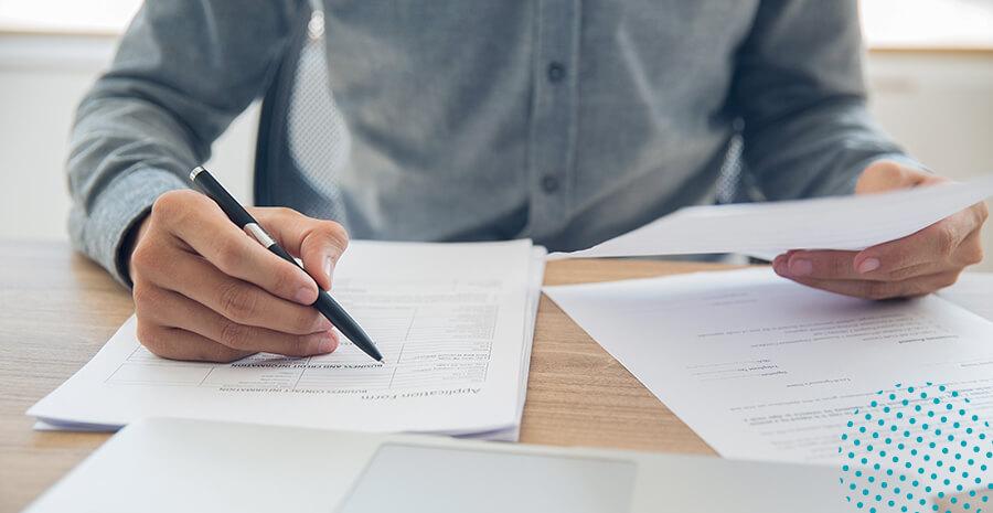 imagem de uma mesa com papéis, um homem segurando uma caneta e escrevendo em um dos papéis e do outro lado segurando uma folha com a descrição de cargos
