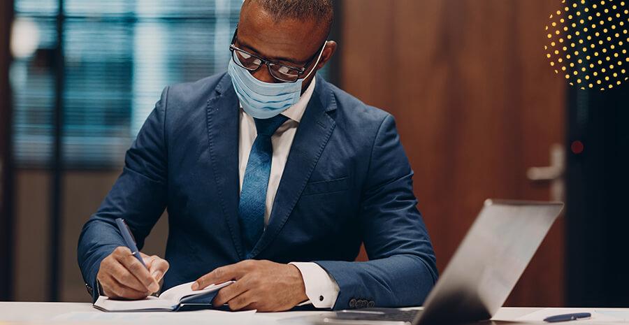 imagem de um homem de terno e máscara escrevendo em um papél em cima de uma mesa