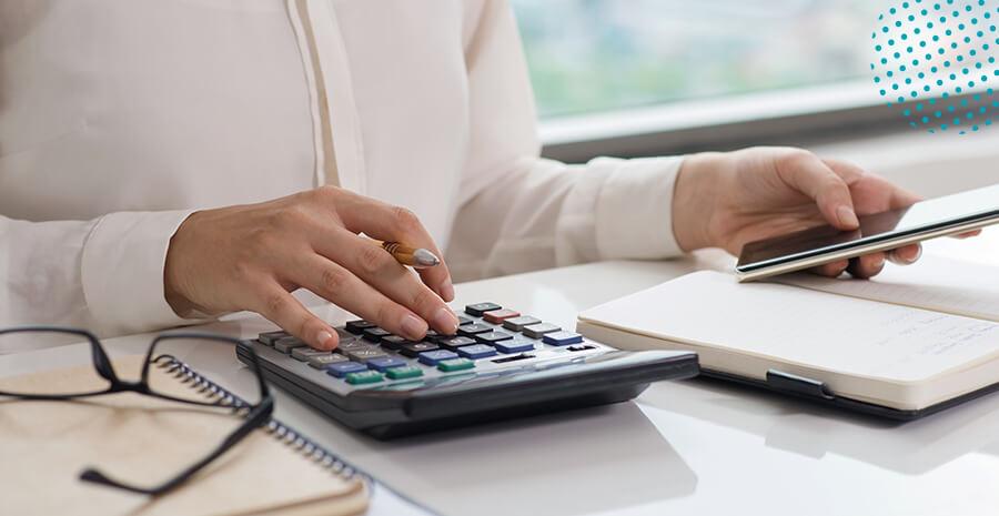 imagem de uma pessoa com uma caneta na mão e uma calculadora na mesa