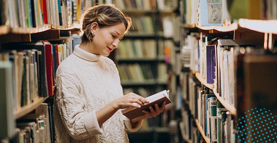 imagem de uma mulher segurando um livro em uma biblioteca