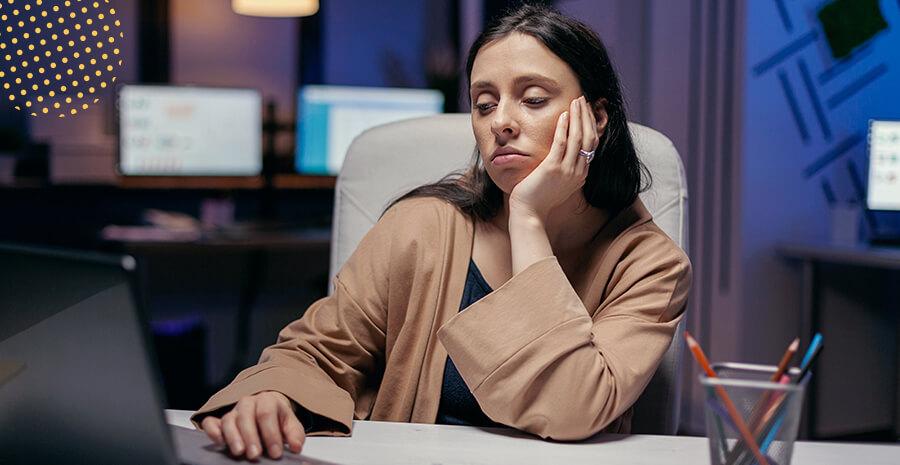 imagem de uma mulher em uma mesa de trabalho com expressão triste e cansada