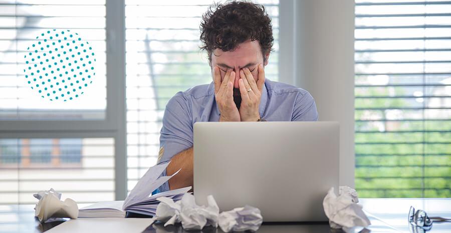 imagem de um homem com as mãos no rosto sentado em frente a uma mesa cheia de papeis amassados